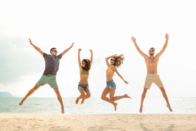 Happy young energetic group of friends jumping at the beach in summer Premium Photo