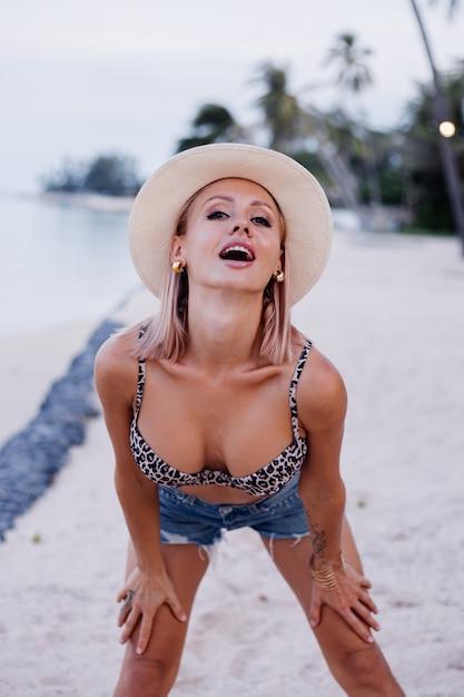ヒョウのトップビキニジーンズのショートパンツと熱帯のエキゾチックなビーチでの古典的な白い帽子の幸せな若いヨーロッパの女性は、休暇旅行のコンセプトで楽しいポーズをとってポーズをとる 無料写真