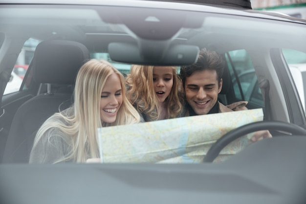 Happy young family in car holding map. Free Photo