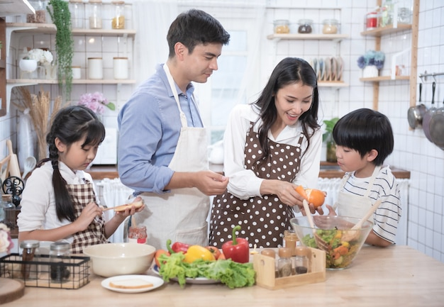 Happy young family have leisure time in kitchen,father help mother cooking,daughter and son eat yam and bread. Premium Photo