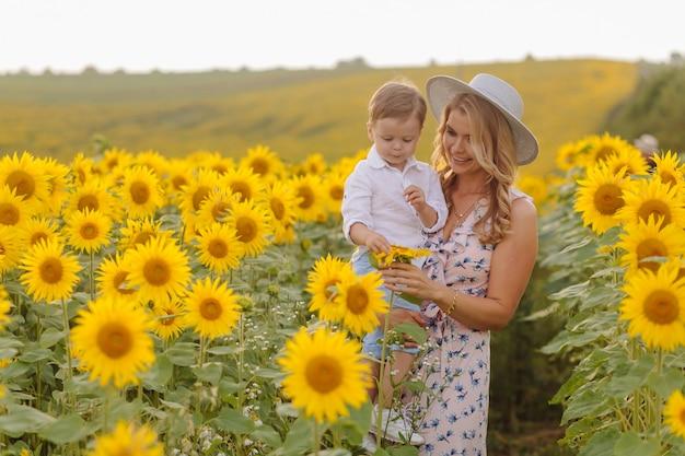 幸せな若い家族、母の父と息子は、ひまわり畑で笑って、抱いて、抱いて 無料写真