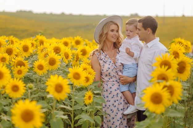 Счастливая молодая семья, мать отца и сына, улыбаются, держатся и обнимаются в поле подсолнечника Бесплатные Фотографии