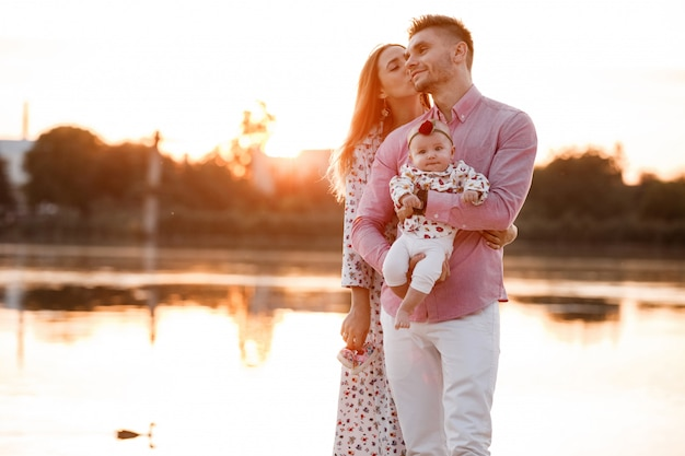 Счастливая молодая семья возле озера, пруд. семья, наслаждаясь жизнью вместе на закате. люди веселятся на природе. семейный вид. мать, отец, ребенок улыбается, проводя свободное время на открытом воздухе Premium Фотографии