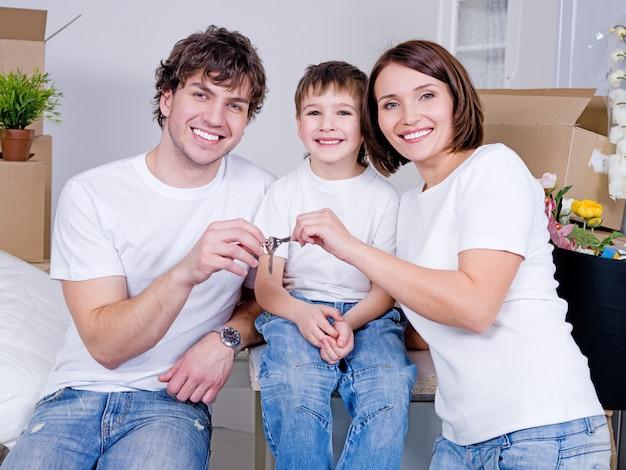 Felice giovane famiglia seduta nel loro nuovo appartamento Foto Gratuite