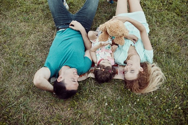 Happy young family spending time together outside in green nature. Free Photo