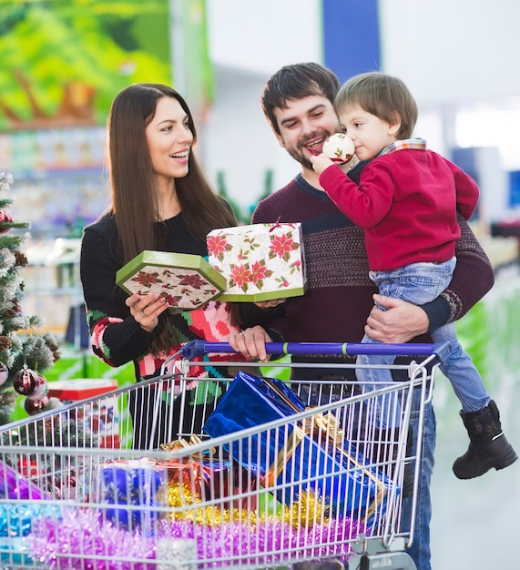 Happy young family in the supermarket chooses gifts for the new year. Premium Photo