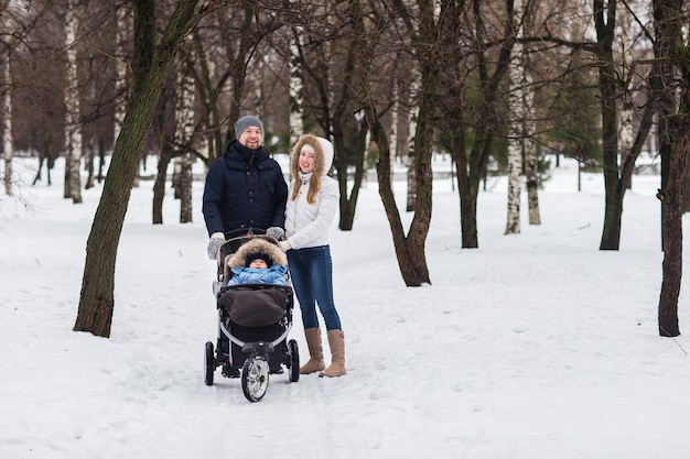 Happy young family walking in the park in winter Premium Photo