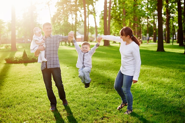 Happy young family walks in the summer park Premium Photo