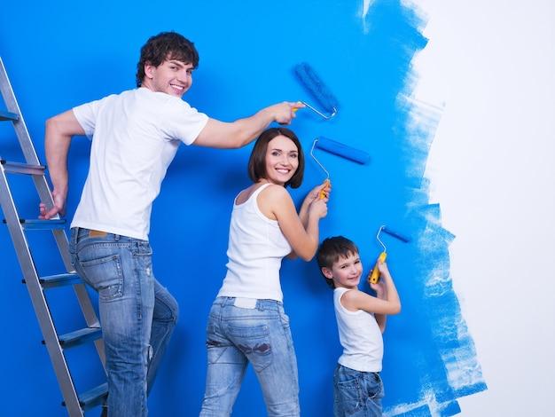 Счастливая молодая семья с маленьким сыном, расписывающим стену Бесплатные Фотографии