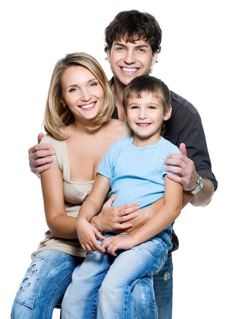 白いスペースでポーズをとってかわいい子供と幸せな若い家族 無料写真