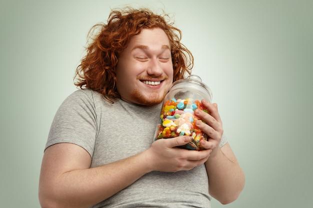 嬉しそうに笑って、目を閉じて幸せな若いデブ肥満男がグッズのガラス瓶で喜び 無料写真