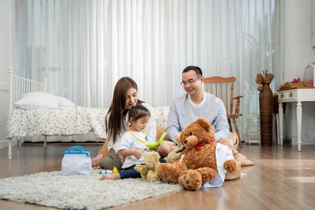 행복 한 젊은 아버지와 어머니와 장난감을 가지고 노는 작은 딸, 거실, 가족, 부모와 사람들 개념에서 바닥에 앉아 프리미엄 사진