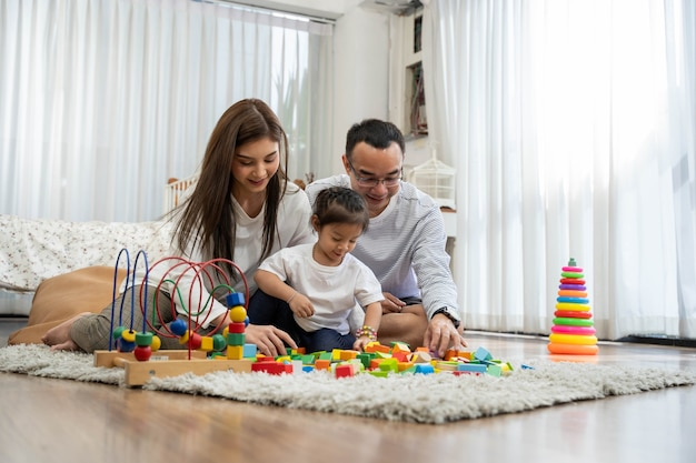 Happy young father and mother and a little daughter playing with toy wooden blocks Premium Photo