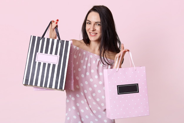 여름 폴카 도트 드레스를 입고 기쁘게 얼굴 표정으로 행복 한 젊은 여성 쇼핑 중독자는 쇼핑백을 보유하고 새 옷을 구입하는 것을 기뻐하며 장미 빛에 포즈를 취합니다. 패키지와 여자 무료 사진