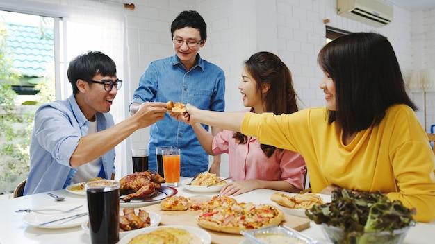 Группа счастливых молодых друзей обедает дома. азиатская семейная вечеринка ест пиццу и смеется, наслаждаясь едой, сидя за обеденным столом вместе дома. праздник праздника и единения. Бесплатные Фотографии