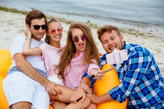 Happy young friends in sunglasses, resting together, taking a selfie on mobile phone Free Photo