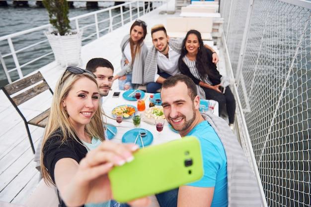 Счастливые молодые друзья сидели за столом и устраивали пикник на природе. Бесплатные Фотографии