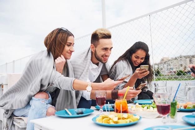 Giovani amici felici erano seduti a un tavolo e facevano un picnic all'aperto. Foto Gratuite