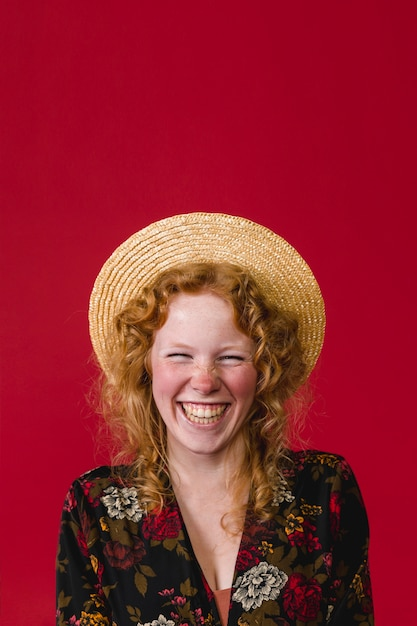 Happy young ginger woman wearing straw hat laughing Free Photo