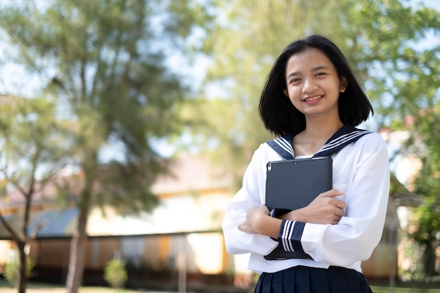 Happy young girl hold laptop at school Premium Photo