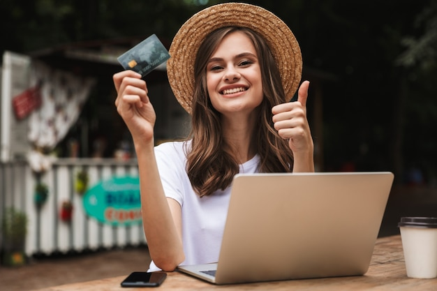 Happy young girl holding plastic credit card while sitting with laptop computer and coffee at the cafe outdoors, showing thumbs up Premium Photo