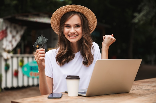 Happy young girl holding plastic credit card while sitting with laptop computer and coffee at the cafe outdoors Premium Photo