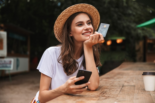 Happy young girl holding plastic credit card while using mobile phone at the cafe outdoors Premium Photo