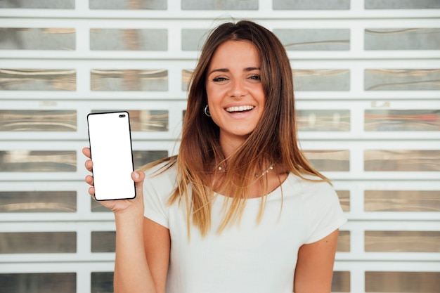 Happy young girl holding smartphone Free Photo