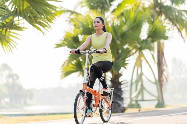 公園で自転車と緑のドレスの幸せな少女 Premium写真