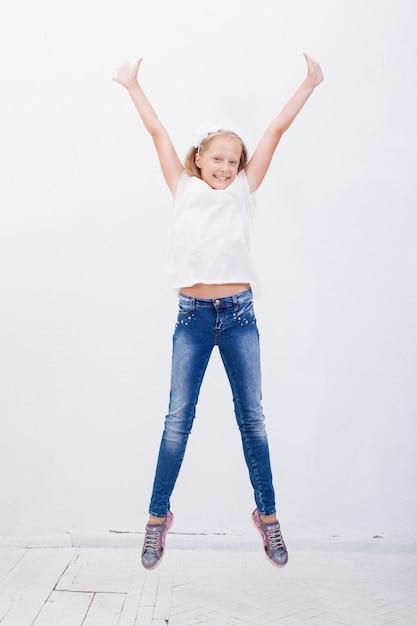 白い背景を飛び越えて幸せな若い女の子 無料写真