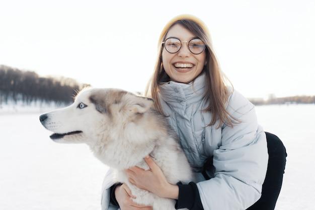 Ragazza felice che gioca con il cane del husky siberiano nel parco di inverno Foto Gratuite