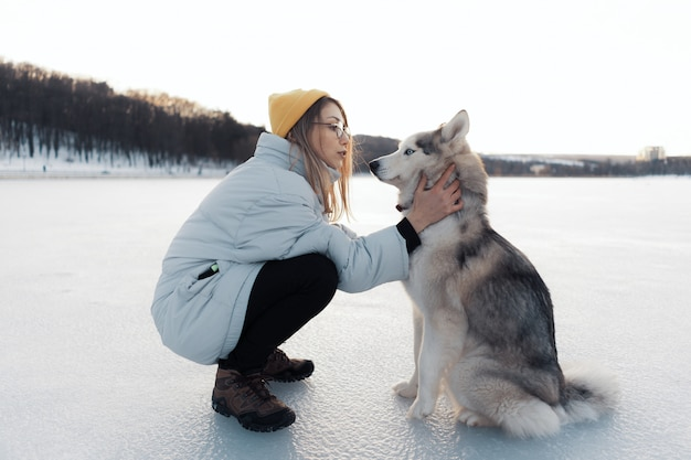 Happy young girl playing with siberian husky dog in winter park Free Photo