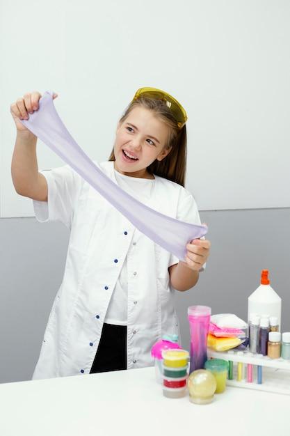 점액을 만드는 행복 한 어린 소녀 과학자 무료 사진