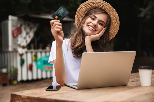 Happy young girl showing plastic credit card while sitting with laptop computer and coffee at the cafe outdoors Premium Photo
