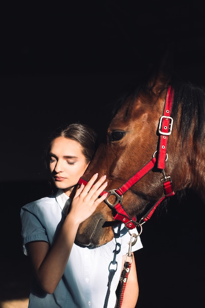Happy young girl sitting outdoors hugging her horse Free Photo