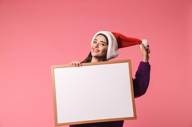 빈 보드를 보여주는 핑크 이상 격리 서 빨간 산타 모자를 쓰고 행복 한 어린 소녀 프리미엄 사진