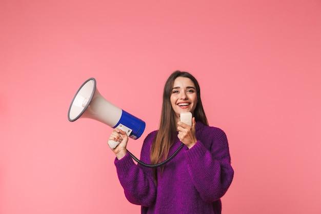 행복 한 어린 소녀 입고 스웨터 서 핑크 이상 격리, 스피커 소리 프리미엄 사진