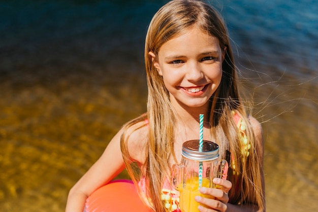 Happy young girl with orange drink on beach vacation Free Photo