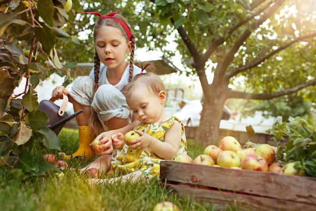 The happy young girland baby during picking apples in a garden outdoors Free Photo