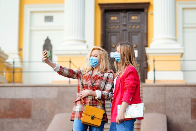Happy young girls taking selfies in city. Premium Photo