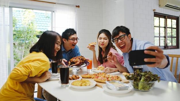 Счастливая молодая группа обедает дома. семейная вечеринка в азии ест пиццу и делает селфи со своими друзьями на дне рождения за обеденным столом вместе дома. праздник праздника и единения Бесплатные Фотографии