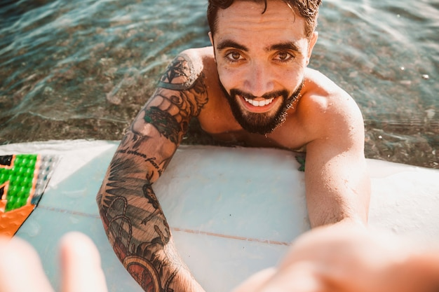 Happy young guy taking selfie and lying on surf board in water Free Photo