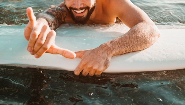 Happy young guy withshaka gesture lying on surf board in water Free Photo