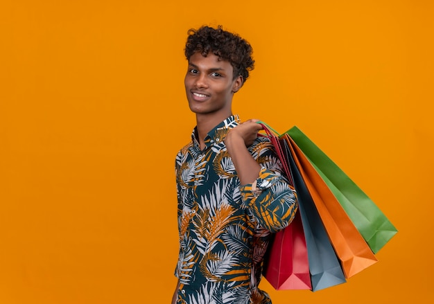 Happy young handsome dark-skinned man with curly hair in leaves printed shirt smilingholding shopping bags while standing Free Photo