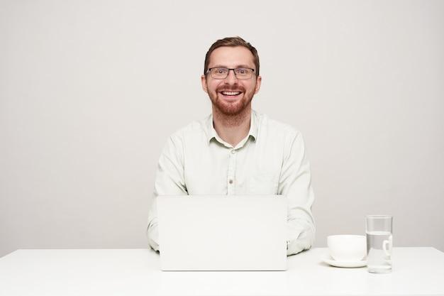 흰색 배경 위에 자신의 노트북으로 작업하는 동안 기꺼이 넓은 미소로 카메라를 찾고 안경에 행복 젊은 잘 생긴 면도되지 않은 남성, 높은 정신 무료 사진
