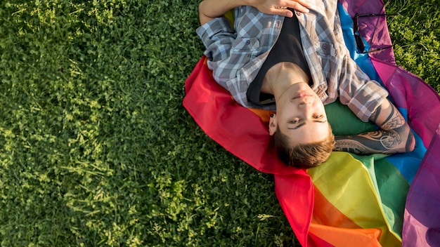 Happy young homosexual lying on glade Free Photo