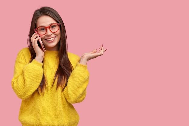 Felice giovane donna ha una conversazione telefonica con la migliore amica, gesticola attivamente mentre racconta cosa è successo con lei durante il giorno Foto Gratuite