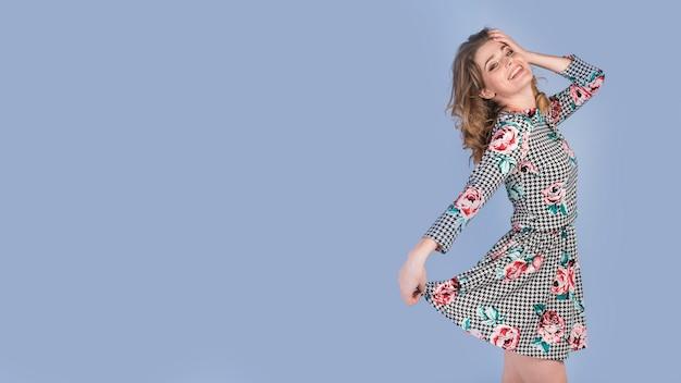 Happy young lady holding skirt of elegant dress Free Photo