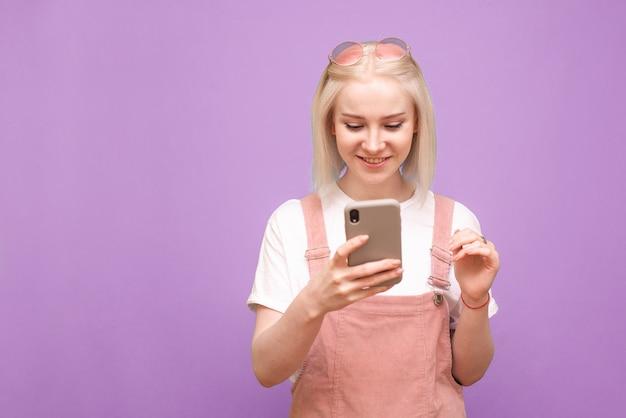 스마트 폰을 사용하고 웃는 귀여운 옷에 행복 젊은 아가씨 프리미엄 사진