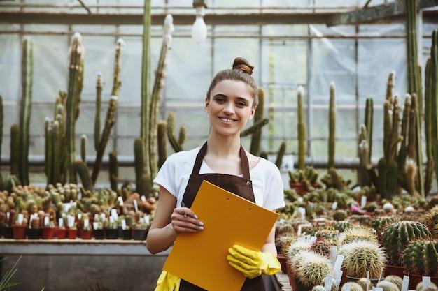 クリップボードを保持している温室に立っている幸せな若い女性 無料写真